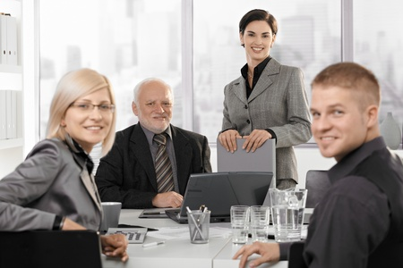 Portrait of smiling businessteam looking at camera, sitting at table on meeting. photo