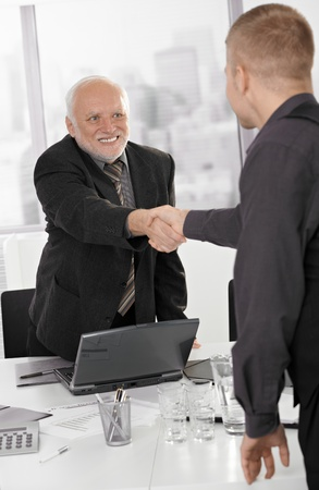 Senior executive shaking hands with businessman in office, smiling. photo