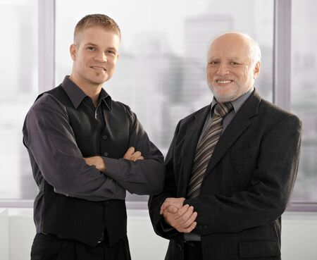 two face: Formal portrait of senior and junior businessmen standing together in office, smiling. Stock Photo