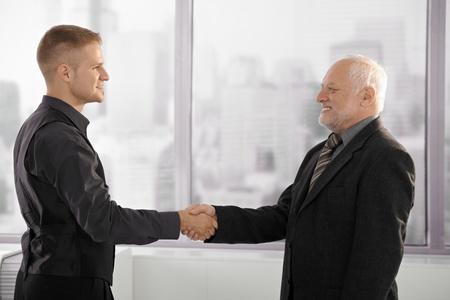 estrechando mano: Senior y hombre de negocios mid-adult, estrechar la mano permanente por la ventana de la Oficina, sonriendo.