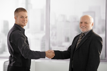 Portrait of senior executive shaking hands with young employee, looking at camera, smiling. Stock Photo