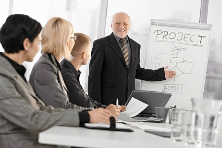 Smiling senior businessman training project success to colleagues, pointing at whiteboard, audience listening. Stock Photo - 8783502