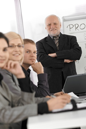 conducting: Portrait of senior businessman standing with arms folded at meeting table, coworkers smiling. Stock Photo