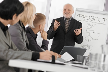 executive courses: Senior businessman presenting on meeting to mid-adult coworkers, smiling, gesturing with both hands.