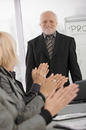 Team applauding senior businessman standing in office with great smile. photo