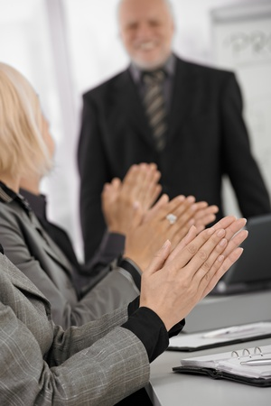businessmeeting: Clapping hands in closeup focus on businessmeeting, senior businessman standing in background. Stock Photo