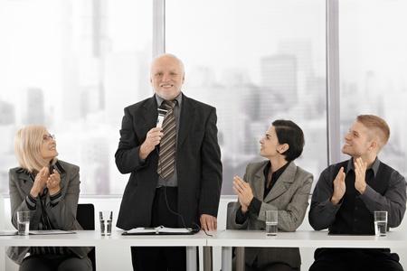 Senior executive stehen, geben Rede mit Mikrofon, sitzen Kollegen klatschen und lächelnd.