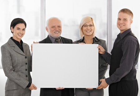 Businessteam holding blank poster for copyspace, smiling, senior executive with young colleagues. photo