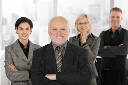 Porträt von Businessteam stehen in Office, Lächeln, senior executive Man im Fokus.