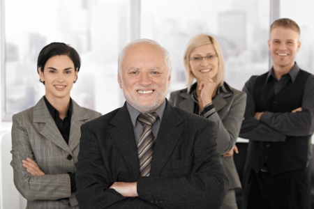 Portrait of businessteam standing in office, smiling, senior executive man in focus. photo