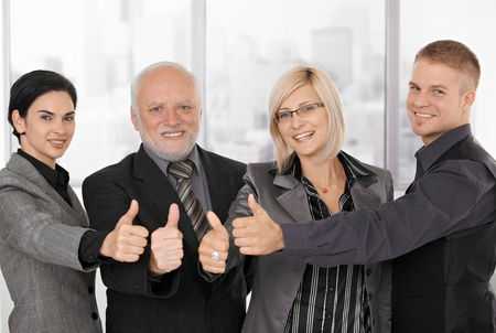 Successful businessteam of different generations smiling, giving thumb ups. photo