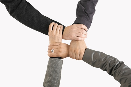 čtyři lidé: Businessteam holding hands, only hands in closeup, expressing unity and teamwork.