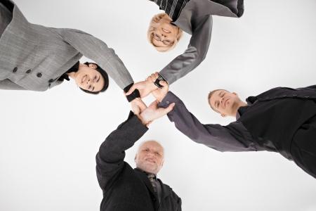 low angle views: Businessteam de todas las generaciones, con las manos en la unidad, que muestra la creaci�n de redes, sonriendo.