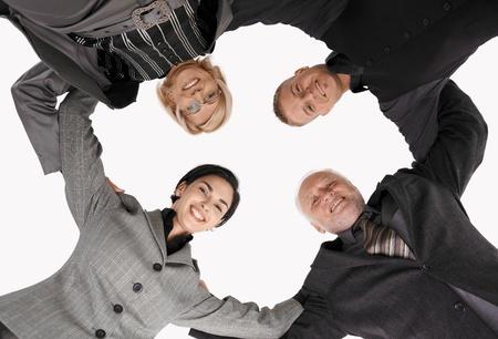 jovenes empresarios: Smart businessteam permanente en huddle, sonriendo, imagen de �ngulo bajo. Foto de archivo
