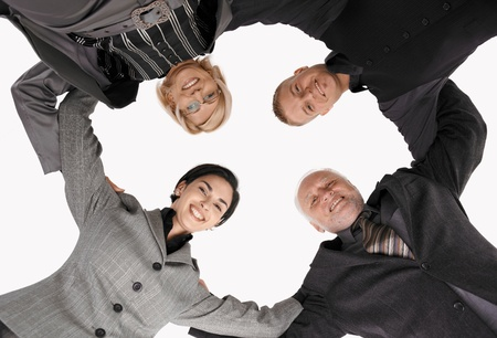 Smart businessteam standing in huddle, smiling, picture from low angle. photo