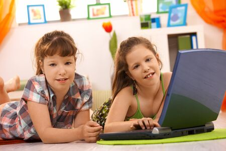 Elementary age girls playing computer game on laptop at home, looking at camera, smiling. photo