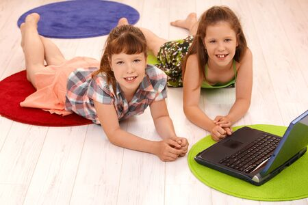 Portrait of smiling small girls lying on floor using laptop computer at home, looking at camera. photo