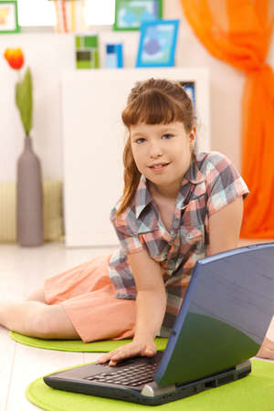 Portrait of little girl using laptop at home, looking at camera. photo