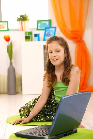 Portrait of little girl sitting on floor with laptop computer, looking at camera, smiling. Stock Photo - 8784516