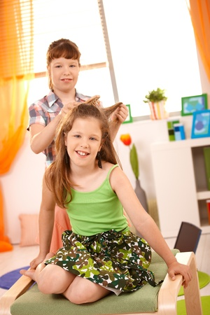 Young girls having fun combing hair at home, smiling at camera. photo