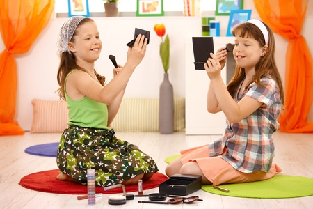 Two young girls playing with makeup at home, smiling. photo