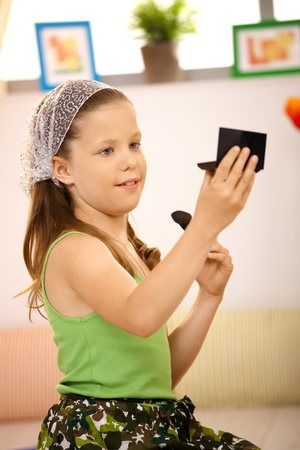 Schoolgirl looking herself in mirror, making up her face at home, sitting on floor. Stock Photo - 8784755