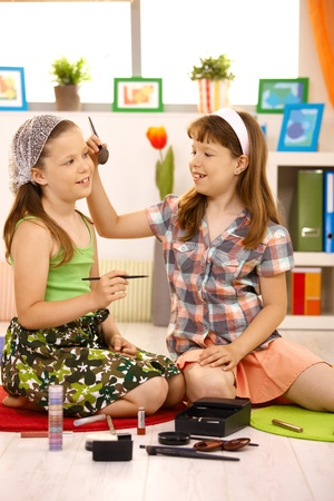 elementary age girls playing with cosmetics at home, having fun. Stock Photo - 8784788