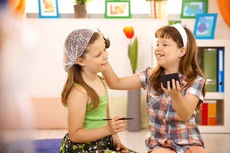 Due giovani ragazze che si diverte con il trucco a casa, sorridente.