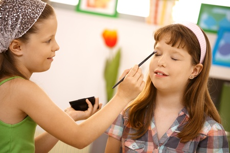 Young girl playing at home, putting makeup on friend, smiling. Stock Photo - 8784794