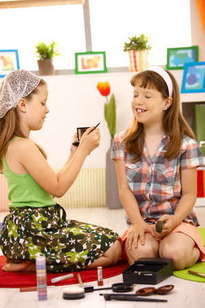 Elementary age girls playing with makeup in living room, laughing. photo