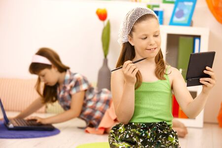 Little girl playing with makeup at home, smiling, other girl using laptop computer in background. Stock Photo - 8784736