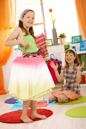 Young girls playing at home fitting dresses, smiling, having fun. photo