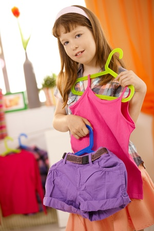 purple dress: Portrait of small girl presenting combination of clothes on hanger, smiling.