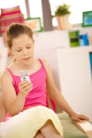 Small girl texting on mobile phone sitting at home. photo