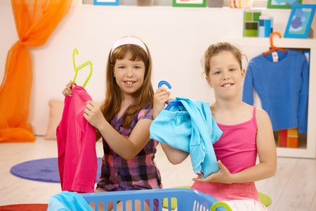 room mate: Schoolgirls sorting clothes, playing at home, sitting on floor, smiling. Stock Photo