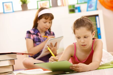 learning by doing: Schoolgirls doing homework at home, writing into exercise books. Stock Photo