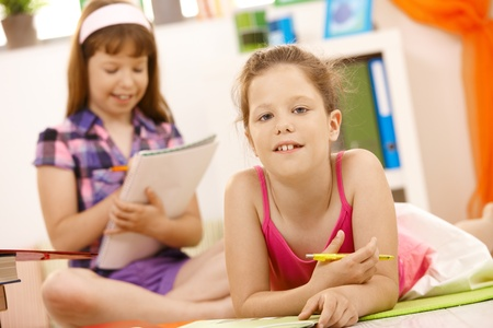 Portrait of elementary age schoolgirl holding pen, friend in background doing homework. Stock Photo - 8784071