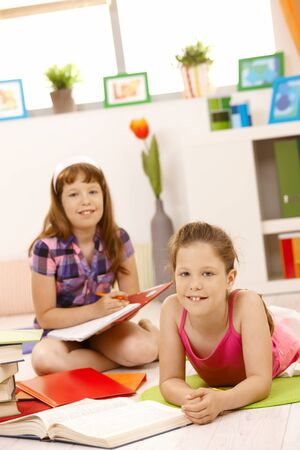 Portrait of girls doing homework together, smiling at camera. Stock Photo - 8783857