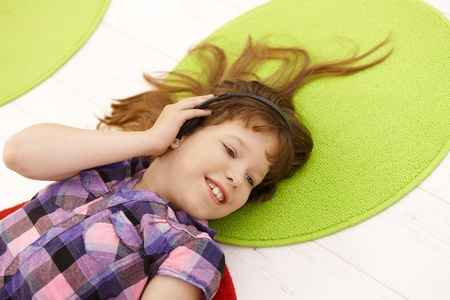 Portrait of schoolgirl with headset, listening to music, smiling, high angle view. photo
