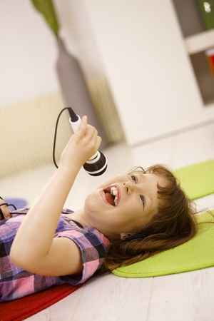 child singing: Young girl singing into microphone, having fun, lying on floor. Stock Photo