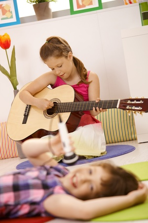 Young girl in focus playing guitar, other girl singing into microphone. photo