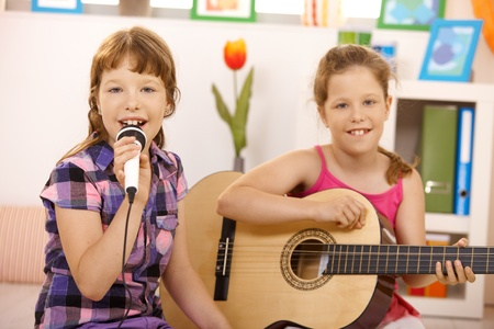 Portrait of young girls performing music, singing and playing guitar, smiling at camera. photo
