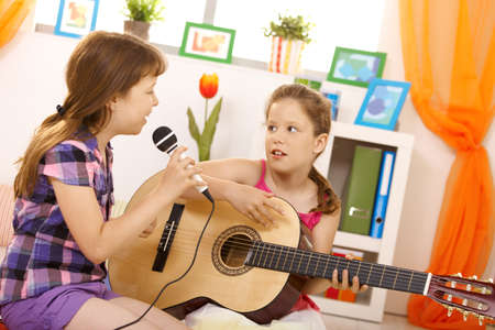 Elementary age girls playing music and singing together at home, having fun. photo