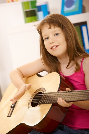 Portrait of little girl with guitar, looking at camera, smiling. Stock Photo - 8784636