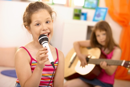 child singing: Portrait of schoolgirl singer looking at camera holding microphone, friend playing guitar in background.