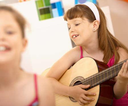 ni�as jugando: Ni�a goza de tocar la guitarra, sonriendo en casa.