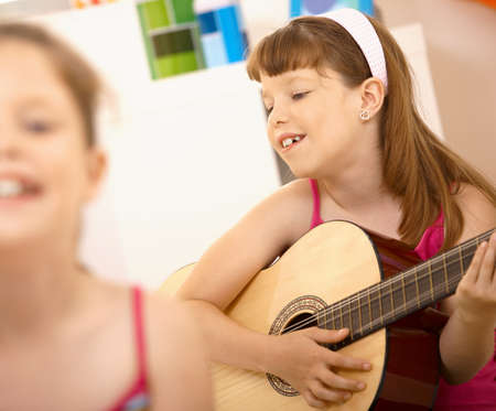 girl playing guitar: Young girl enjoying playing guitar, smiling at home.