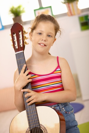 females only: Cute schoolgirl holding guitar, looking at camera, smiling. Stock Photo