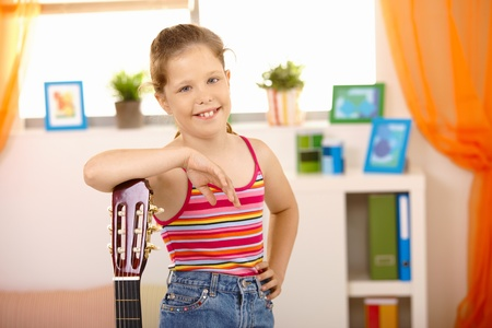 Portrait of happy schoolgirl posing with guitar smiling at camera. photo