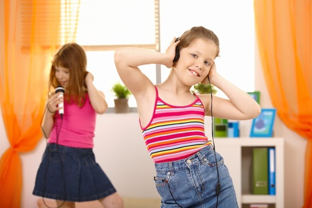 child singing: Girls enjoying music, listening via headphones, singing with microphone, dancing. Stock Photo